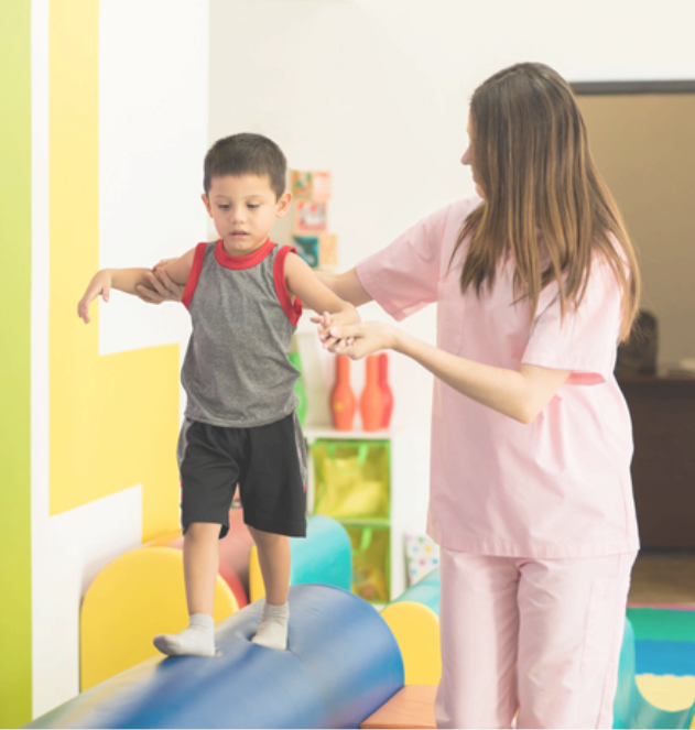 Female-therapist-helping-a-kid-to-maintain-balance-while-walking-on-a-beam-in-a-therapy-center